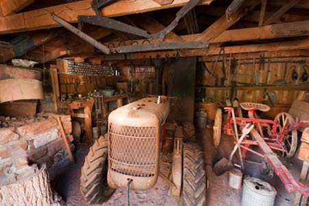 Interior of garage at Gifford Homestead showing old tractor and farm equipment