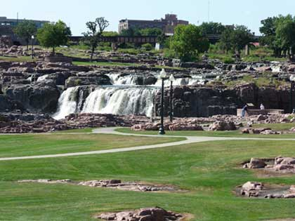 View of Sioux Falls with grass in front of water falls